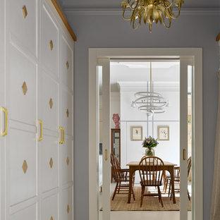 Aménagement d'un vestibule contemporain de taille moyenne avec un mur gris, béton au sol, une porte coulissante, une porte blanche et un sol blanc.
