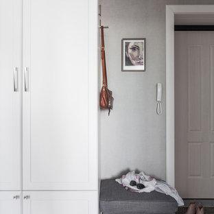 Réalisation d'une petit porte d'entrée tradition avec un mur gris, sol en stratifié, une porte simple, une porte en bois clair et un sol beige.