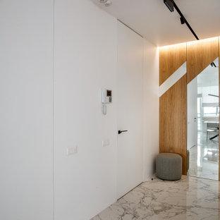 На фото: большие узкие прихожие в современном стиле с белыми стенами, серым полом, одностворчатой входной дверью и белой входной дверью