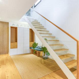Aménagement d'un couloir éclectique de taille moyenne avec un mur blanc et un sol en bois clair.