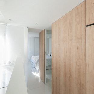 Réalisation d'un petit couloir design avec un mur blanc, un sol en linoléum et un sol blanc.