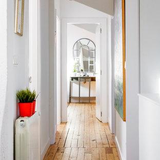 Ejemplo de recibidores y pasillos bohemios, de tamaño medio, con paredes blancas, suelo de madera en tonos medios y suelo marrón
