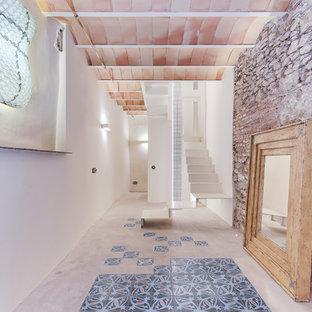 Ejemplo de recibidores y pasillos mediterráneos, de tamaño medio, con paredes blancas y suelo gris