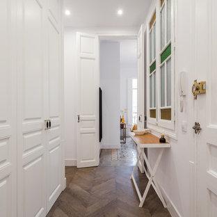 Foto de recibidores y pasillos clásicos con paredes blancas, suelo de madera oscura y suelo marrón