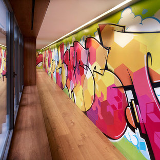 Photo of a large modern hallway in Madrid with multi-coloured walls, medium hardwood floors and brown floor.