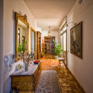 Diseño de recibidores y pasillos mediterráneos, grandes, con paredes blancas, suelo de baldosas de terracota y suelo rojo