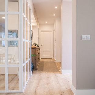 Ejemplo de recibidores y pasillos minimalistas, de tamaño medio, con paredes blancas, suelo de madera clara y suelo marrón