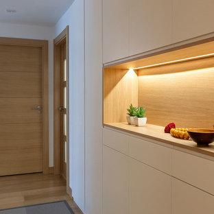 Foto di un piccolo ingresso o corridoio minimalista con pareti bianche, parquet chiaro e pavimento giallo