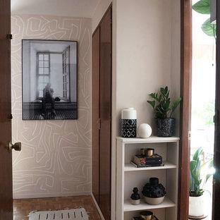 Inspiration pour un couloir bohème avec un mur rose, un sol en bois brun et un sol marron.
