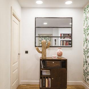 Imagen de recibidores y pasillos tropicales, pequeños, con paredes blancas y suelo de madera en tonos medios