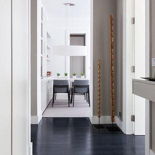 Diseño de recibidores y pasillos contemporáneos con paredes grises, suelo de madera oscura y suelo negro