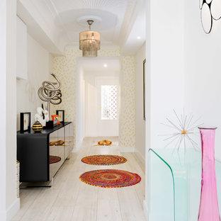 Ejemplo de recibidores y pasillos eclécticos, de tamaño medio, con paredes blancas, suelo de madera clara y suelo beige