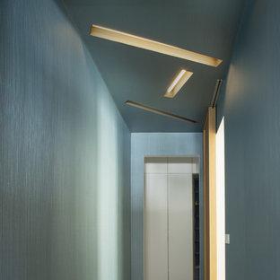Réalisation d'un couloir design de taille moyenne avec un mur bleu, un sol en carrelage de porcelaine et un sol gris.