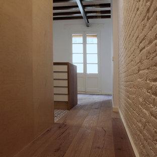 Inspiration pour un couloir urbain de taille moyenne avec un mur blanc, un sol en bois brun, un plafond voûté et un mur en parement de brique.