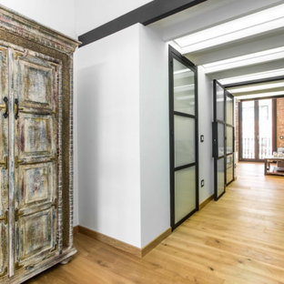 Inspiration för små industriella hallar, med vita väggar, mellanmörkt trägolv och brunt golv