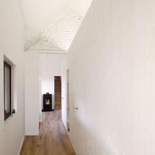 他の地域の小さい北欧スタイルのおしゃれな廊下 (白い壁、ラミネートの床、茶色い床) の写真