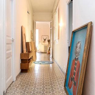 バルセロナの広いエクレクティックスタイルのおしゃれな廊下 (白い壁、セラミックタイルの床、マルチカラーの床) の写真