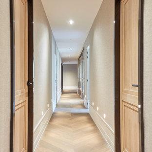 На фото: большой коридор в стиле современная классика с бежевыми стенами, светлым паркетным полом, коричневым полом и обоями на стенах с
