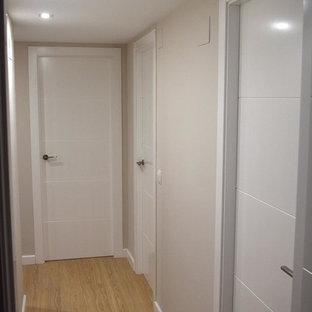 Idee per un ingresso o corridoio moderno di medie dimensioni con pareti bianche, pavimento in legno massello medio e pavimento marrone
