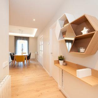 Ejemplo de recibidores y pasillos minimalistas, de tamaño medio, con paredes blancas, suelo de madera en tonos medios y suelo marrón