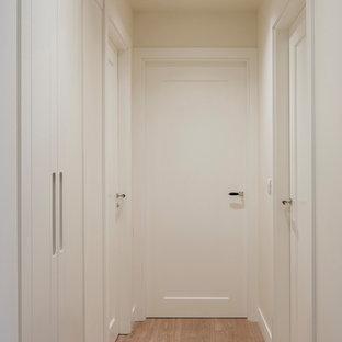ビルバオの中サイズのトランジショナルスタイルのおしゃれな廊下 (ベージュの壁、ラミネートの床、茶色い床) の写真