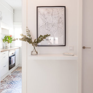 Inspiration for a small beach style hallway in Madrid with white walls, light hardwood floors and grey floor.