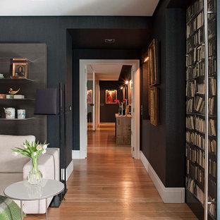 Cette photo montre un couloir chic avec un mur noir et un sol en bois brun.