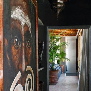 Diseño de recibidores y pasillos exóticos, de tamaño medio, con paredes negras y suelo de baldosas de terracota