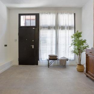 マドリードのエクレクティックスタイルのおしゃれな廊下 (無垢フローリング、グレーの床、レンガ壁) の写真