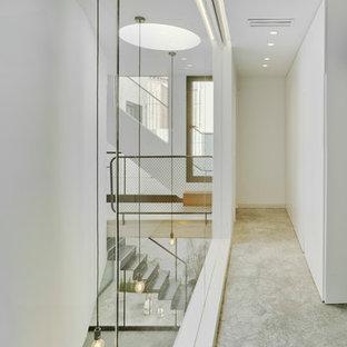 Modelo de recibidores y pasillos modernos con paredes blancas, suelo gris y suelo de cemento