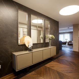 Bild på en stor funkis hall, med grå väggar, mellanmörkt trägolv och brunt golv