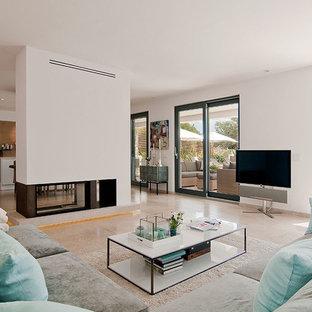 マヨルカ島の大きい地中海スタイルのおしゃれなファミリールーム (白い壁、ライムストーンの床、据え置き型テレビ、両方向型暖炉) の写真