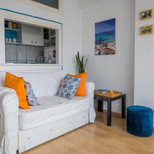 Idee per un piccolo soggiorno mediterraneo chiuso con pareti bianche, pavimento in legno massello medio, nessun camino e nessuna TV