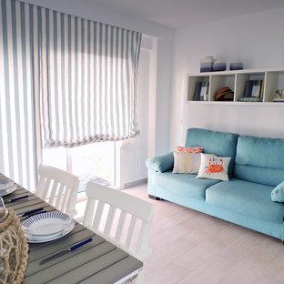 Modelo de sala de estar abierta, mediterránea, pequeña, con paredes blancas, suelo de baldosas de cerámica, televisor colgado en la pared y suelo beige