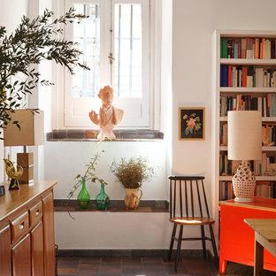 Modelo de sala de estar con biblioteca abierta, mediterránea, pequeña, sin chimenea y televisor, con paredes blancas y suelo de baldosas de terracota