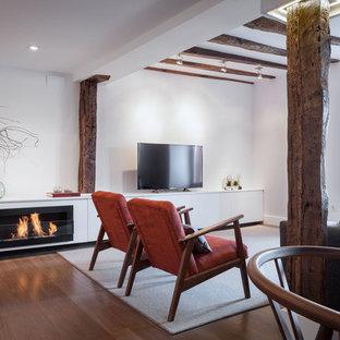 Imagen de sala de estar abierta, mediterránea, de tamaño medio, con paredes blancas, suelo de madera en tonos medios, chimenea lineal, marco de chimenea de metal, televisor independiente y suelo marrón