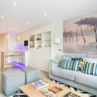 Imagen de sala de estar tipo loft, moderna, pequeña, con paredes blancas, suelo de baldosas de porcelana y televisor colgado en la pared