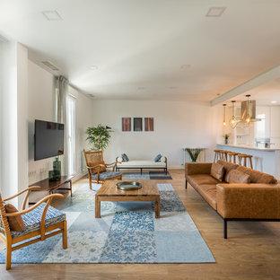 Imagen de sala de estar abierta, costera, grande, sin chimenea, con paredes blancas, suelo de madera en tonos medios y televisor colgado en la pared