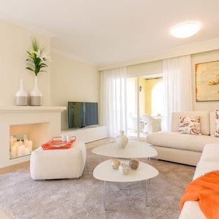 Diseño de sala de estar abierta, costera, de tamaño medio, con paredes beige, chimenea tradicional, marco de chimenea de yeso, televisor independiente y suelo beige