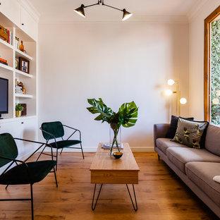 Ejemplo de sala de estar cerrada, nórdica, con paredes beige, suelo de madera en tonos medios, televisor independiente y suelo marrón