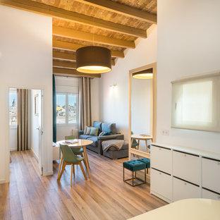 Modelo de sala de estar abierta, clásica renovada, con suelo de madera en tonos medios y paredes blancas