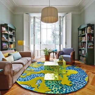 Ejemplo de sala de estar con biblioteca cerrada, ecléctica, de tamaño medio, sin chimenea, con paredes azules y suelo de madera en tonos medios