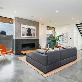 Esempio di un grande soggiorno moderno stile loft con libreria, pareti multicolore, pavimento in cemento, camino sospeso, cornice del camino in cemento, nessuna TV e pavimento grigio