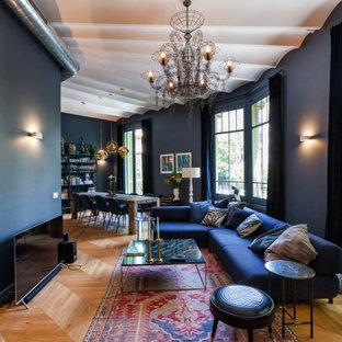 Foto de sala de estar abierta, mediterránea, con paredes negras, suelo de madera en tonos medios y televisor independiente