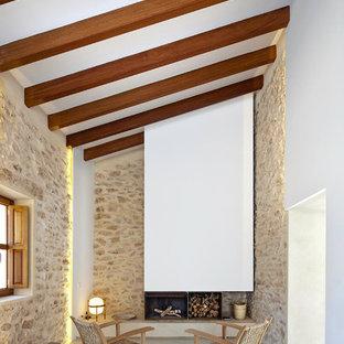 他の地域の中くらいの地中海スタイルのおしゃれな独立型ファミリールーム (コンクリートの床、標準型暖炉、茶色い壁、金属の暖炉まわり、テレビなし) の写真