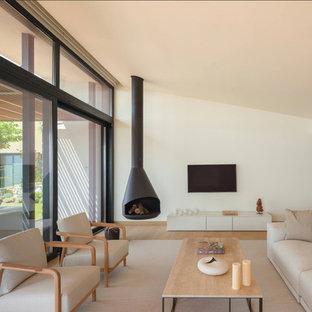 Immagine di un soggiorno mediterraneo di medie dimensioni e aperto con pareti bianche, parquet chiaro, camino sospeso, cornice del camino in metallo, TV a parete e pavimento beige