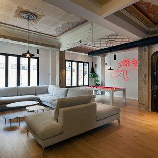 Ejemplo de sala de estar abierta, actual, grande, con paredes blancas, suelo de madera en tonos medios, televisor colgado en la pared y suelo beige