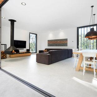 Ejemplo de sala de estar abierta, actual, con paredes blancas, suelo de cemento, chimeneas suspendidas, televisor colgado en la pared y suelo gris