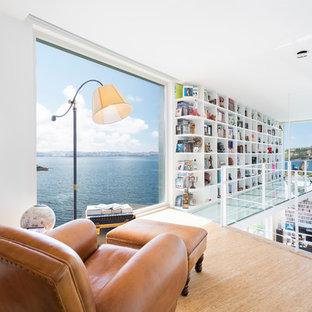 Modelo de sala de estar con biblioteca tipo loft, actual, de tamaño medio, sin chimenea y televisor, con paredes blancas y suelo de madera clara