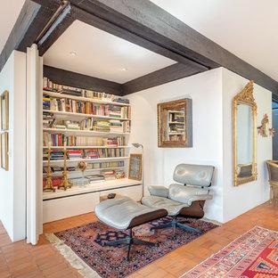 Imagen de sala de estar con biblioteca abierta, mediterránea, pequeña, sin chimenea y televisor, con paredes blancas y suelo de baldosas de terracota